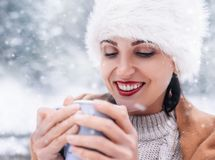 Magic winter moments - woman portrait with cup of hot tea in sno Stock Photography
