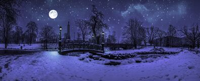Free Magic Winter Night With Starry Sky And Full Moon In Snowy Park With Beautiful Bridge Over Small Pond, Street Light And Covered In Stock Photo - 212288140