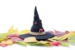 Magic witch hat among autumn leaves on a white backgroun Royalty Free Stock Photo