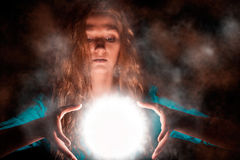 Magic woman with light sphere. Young woman making magic, looking down at bright light sphere between her palms. Misty background Royalty Free Stock Image