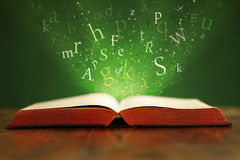 Magic words. Book or bible on table with flying letters on green background Royalty Free Stock Photo