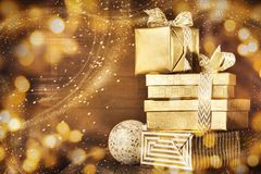 Shiny gold boxes with Christmas presents. Magical arrangement of stacked Christmas gold presents in bright sparkles Royalty Free Stock Photo