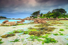 Magical Atlantic ocean coast with granite stones, Perros-Guirec, France. Amazing rocky beach with pink granite stones and wonderful green gardens on the coast Stock Image