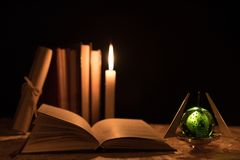 A magical ball, a scroll, a candle and an old book in the dark of the night Stock Photography