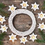 Christmas Border: cozy warm lights garland stars and fir branches around a white wreath on a rustic wooden background. top view. royalty free stock photos