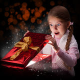 Magical Christmas gift. The girl  with abstract light from a gift box. Emotion a surprise. A dark background Royalty Free Stock Photography