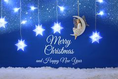 Magical christmas image of little white fairy with glitter wings sitting on the moon over blue background and silver snowflake gar Royalty Free Stock Images