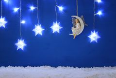 Magical christmas image of little white fairy with glitter wings sitting on the moon over blue background and silver snowflake gar. Land stock image