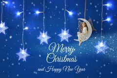 Magical christmas image of little white fairy with glitter wings sitting on the moon over blue background and silver snowflake gar. Land Royalty Free Stock Photo