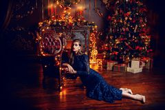 Magical christmas night. Beautiful woman in evening dress celebrates Christmas in luxurious apartments decorated christmas lights Royalty Free Stock Images