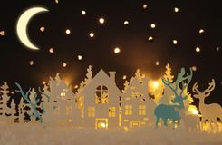 Magical Christmas paper cut winter background landscape with houses, trees, deer and snow in front of night starry sky background. Magical Christmas paper cut royalty free illustration