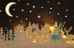 Magical Christmas paper cut winter background landscape with houses, trees, deer and snow in front of night starry sky background. Magical Christmas paper cut stock illustration
