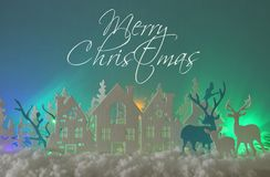 Magical Christmas paper cut winter background landscape with houses, trees, deer and snow in front of northern lights background. stock illustration