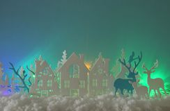 Magical Christmas paper cut winter background landscape with houses, trees, deer and snow in front of northern lights background. Magical Christmas paper cut royalty free stock photography