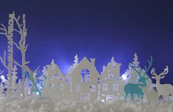 Magical Christmas paper cut winter background landscape with houses, trees, deer and snow in front of white lights background. Magical Christmas paper cut stock illustration