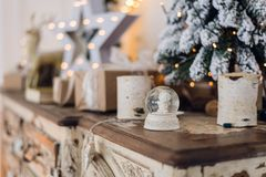 Magical Christmas snow globe with little angel statue inside. Christmas decoration around. Shallow depth of field with Stock Photo