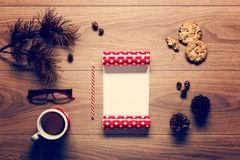 Magical christmas theme background, pine cones, coffee, cookies and an empty letter to santa Stock Images
