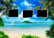 Magical coast. Tropical coast, beach with photo frames on clothesline and hang palm trees. View of the Sea, the island green and the sky with large clouds Royalty Free Stock Photo