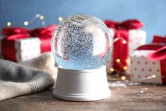 Magical empty snow globe with Christmas presents. On wooden table royalty free stock images