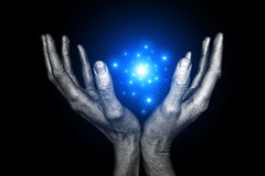 Magical energy. Men's silver hand with magical energy on a black background Stock Photography