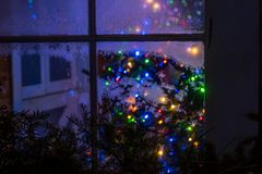 A magical fabulous winter window with toys and Christmas tree lights. stock image
