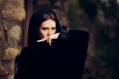 Mysterious Dark Witch in Black Hooded Cape Royalty Free Stock Image