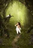 Magical forest. The girl with a doll in hands looks at the cat Stock Photography