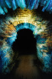Magical gateway. Ancient stone arch illuminated with blue and yellow light to create a magical and mysterious gateway into the dark Stock Image