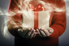 Magical gift box. With red bow lies in the hands. Christmas concept Stock Photography