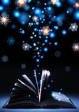 Magical glow coming from the open book in the dark winter background. An open book lies in the dark, it comes from the glow of the lights. The snowflakes float Royalty Free Stock Photography
