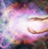 Magical Healing Energy. Healing hands with vivid magical background of color, sparkles and swirling light royalty free stock images