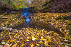 A magical landscape with a waterfall in the autumn forest & x28;harmo Royalty Free Stock Image