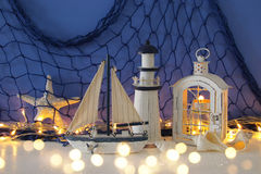Magical lantern with candle light and wooden boat on the shelf. Nautical concept.  Royalty Free Stock Photography