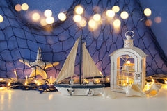 Magical lantern with candle light and wooden boat on the shelf. Nautical concept.  Stock Images