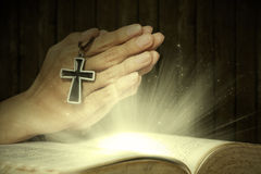 Magical light bible and prayer hands Royalty Free Stock Photo