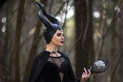 Magical Maleficent Character Posing with Crook in Spring Empty Forest. Horizontal Image Composition royalty free stock image