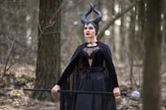 Magical Maleficent Character Posing with Crook in Spring Empty Forest. Horizontal Image Composition royalty free stock photo