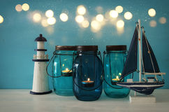 Magical mason jars whith candle light and wooden boat on the shelf. Glitter overlay. Nautical concept Stock Images