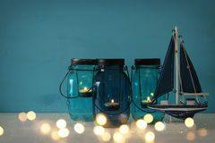 Magical mason jars whith candle light and wooden boat on the shelf. Glitter overlay. Nautical concept Stock Photography