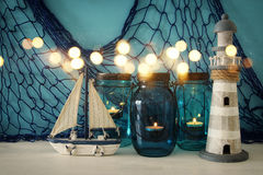 Magical mason jars whith candle light and wooden boat on the shelf. Glitter overlay Royalty Free Stock Images