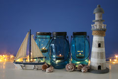 Magical mason jars whith candle light and wooden boat on the shelf. Nautical concept Stock Photo