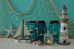Magical mason jars whith candle light and wooden boat on the shelf. Nautical concept Stock Image