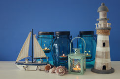 Magical mason jars whith candle light and wooden boat on the shelf. Nautical concept Royalty Free Stock Photos