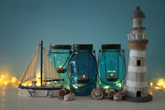 Magical mason jars whith candle light and wooden boat on the shelf. Nautical concept Stock Photos