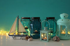 Magical mason jars whith candle light and wooden boat on the shelf. Nautical concept Stock Images