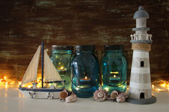 Magical mason jars whith candle light and wooden boat on the shelf. Nautical concept.  Stock Photos