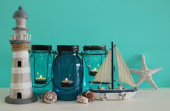 Magical mason jars whith candle light and wooden boat on the shelf. Nautical concept.  Royalty Free Stock Photography