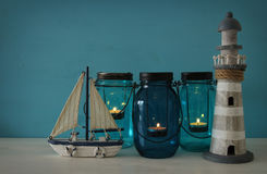 Magical mason jars whith candle light and wooden boat on the shelf. Nautical concept.  Royalty Free Stock Image
