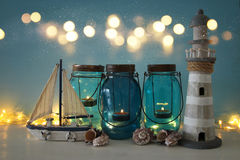 Magical mason jars whith candle light and wooden boat on the shelf. Nautical concept.  Royalty Free Stock Photos