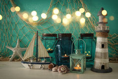 Magical mason jars whith candle light and wooden boat on the shelf. Nautical concept Royalty Free Stock Images